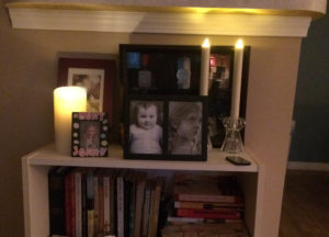 Three Luminara candles flickering on a bookcase